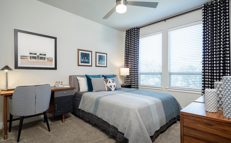 Bedroom with ceiling fan and large windows
